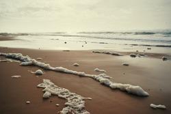 Sea foam on the beautiful sand Atlantic ocean beach.