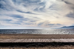 Sea in Agia Anna beach, in Naxos islands, flows like horizontally across the field of view, in front of sandy beach with wooden pathway, under an overcast sky.