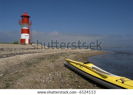 Sea-Kayak beached near small red and white light house. Jutland, Denmark - stock photo