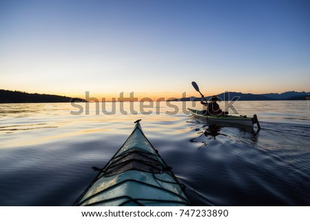Sea kayaking in the ocean during a colorful and vibrant sunset. Taken in Jericho, Vancouver, British Columbia, Canada. #747233890