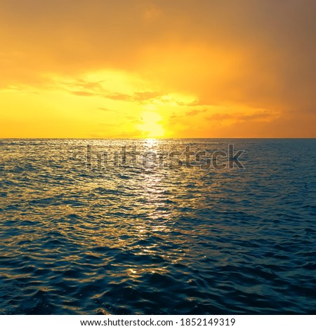 Sea landscape with sunset or sunrise. Only water, waves and a cloudy sky with the sun breaking through the clouds and the sun's rays reflecting off the waves Foto stock ©