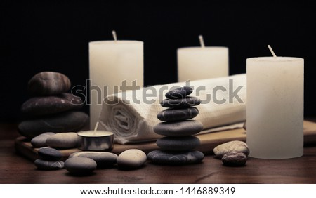 sea massage stones wite napking and candles on wooden surface in composition, spa, relax, cosy ambience, equilibrium concept