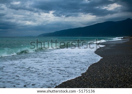 Sea, mountains and dark sky with clouds