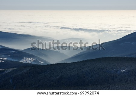 Sea of clouds and coast of foggy hills