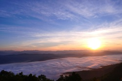 Sea of mist scenary at sunrise time. Beautiful blue sky with cloud. Silhouette mountains.