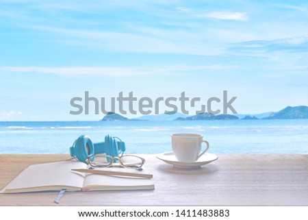 Sea of Sky and Clouds of White With a cup of coffee, glasses, blue earphones, diary, notebook and pencil to save your holiday in Thailand. Feelings, sadness, loneliness, nostalgia. #1411483883
