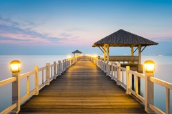 Sea or nature background with sunset and sky at twilight. Perspective view of wood bridge and pavilion. Asia travel destination in Chonburi of Thailand called Bangsaen Beach for holiday and vacation.