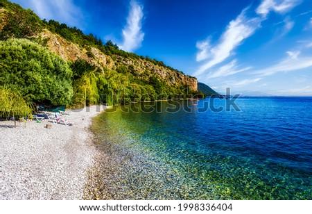 Sea pebble beach on a clear summer day. Pebble beach at sea. Sea beach lagoon. Tropical island sea pebble beach