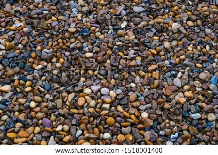 Sea pebbles. Background of pebbles. Stones. Multicolored pebbles. Sea shore.