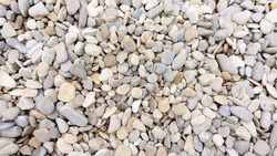 Sea pebbles background. The texture of small black sea pebbles. Beautiful design template with mosaic sea pebbles background. Sea pebbles in landscaping, garden paths, rockeries.