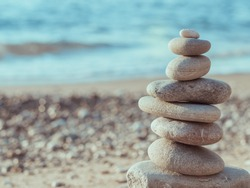 Sea pebbles tower closeup. Pebbles sculpture made on Barcelona beach. Beautiful soft background