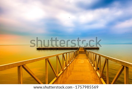 Sea pier in morning sunrise. Morning pier sunrise view. Pier in morning sunrise scene. Sunrise pier