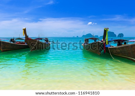Sea resort. Blue water, cloudy sky and traditional fishing boats. Travel background