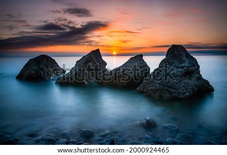 Sea rocks at sunset landscape. Sunset sea rocks. Sunset over the sea. Sunset sea landscape