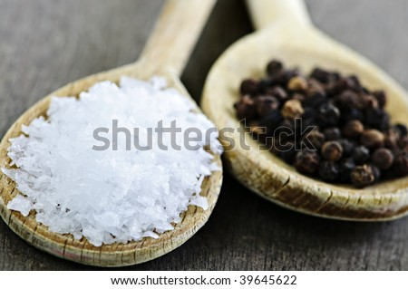 Sea salt and whole peppercorns on wooden spoons