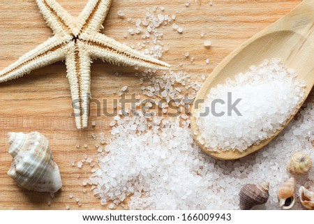 Sea Salt Crystals In Wooden Spoon With Sea Shells And Starfish On Wooden Background