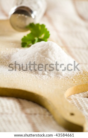 Sea salt on cloth and wooden plate in kitchen.