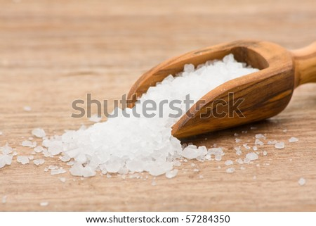 Sea salt poured from wooden scoop on table