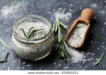 Sea salt scented herb rosemary on black stone background, vintage style