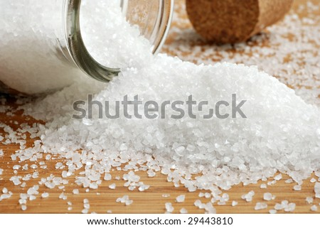 Sea salt spilling from glass bottle onto bamboo surface.  Cork bottle stopper in background.  Macro with shallow dof.