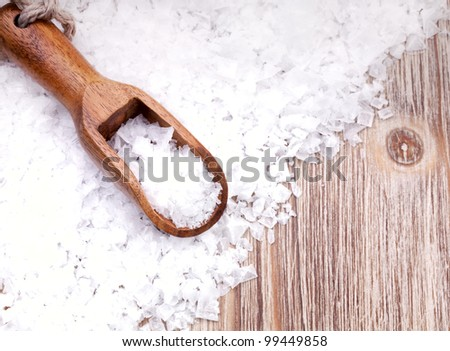 Sea salt with wooden scoop on vintage  surface