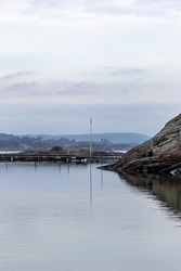 Sea scape on grey day with flag pole and lamp post reflecting in water