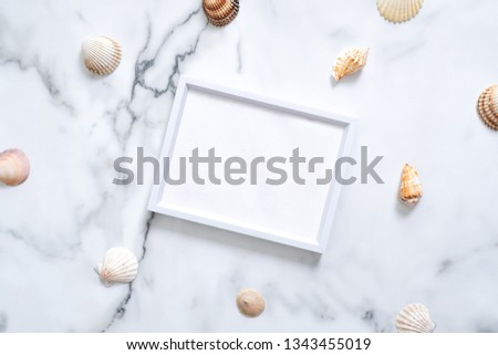 Sea shells and blank picture frame with copy space for your text on marble background. Summer vacation concept. Flat lay, top view, overhead.
