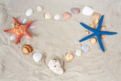 sea shells and stars on sand arrange as a heart
