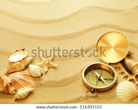 sea shells old compass with sand as background