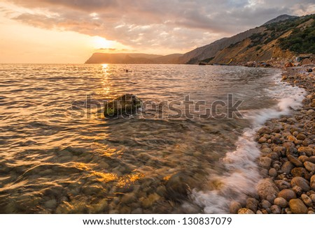 Sea, shore and stones. Seascape at sunset.