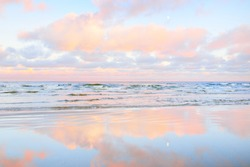 Sea shore at sunset. Clear blue sky, colorful glowing pink clouds, soft light. Symmetry reflections on water, natural mirror, water surface texture. Weather, climate change, nature. Idyllic seascape