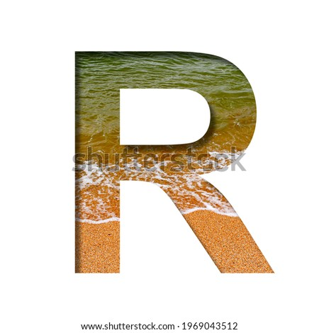 Sea shore font. The letter R cut out of paper on a background of the beach of seashore with coarse sand and emerald water. Set of decorative natural fonts. Photo stock ©