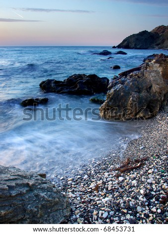 Sea stone and waves during sundown. Natural composition