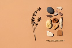 Sea stones and twigs of dry grass on a paper background of beige sand color. Space for text, concept for natural, organic decor, spa, wellness. Blank invitation card, postcard light terracotta colors.
