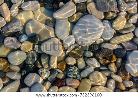 Sea stones in the sea water. Pebbles under water. The view from the top. Nautical background. Clean sea water. Transparent sea. #732396160