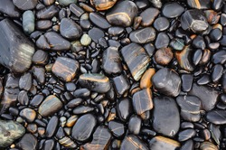 Sea stones or the wet smooth black stone, black pebbles on the beach as background.Tarutao National Park,Thailand