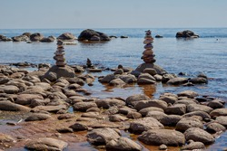 sea stones stacked in the form of pyramids against the background of the blue sea . High quality photo