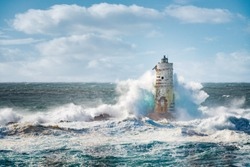 Sea storm on Lighthouse Mangiabarche situated in Calasetta, Sardinia, Italy.