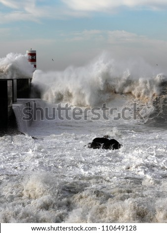 Sea storm with waves crashing against the pier at the mouth of the Douro River on a sunny day; Focus on the 1st plane/foreground