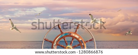 Sea sunset during the calm in pastel colors with the steering wheel of skipper, cloudy sky and seagulls. Panorama of seascape for your concept of a romantic sea cruise on a ship around the world.