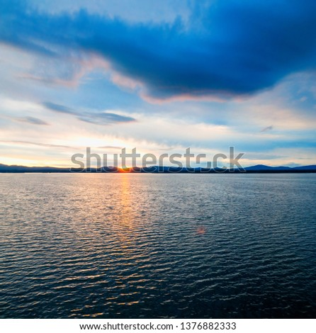 Sea sunset landscape. Sea water surface lit by sunset light. Summer sunny water scene in colorful tones. Sea summer nature with mountain range at the horizon #1376882333