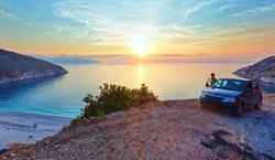 Sea sunset view of Myrtos Beach and woman near car (Greece,  Kefalonia, Ionian Sea). Beautiful natural summer vacation by car travel to sea concept.