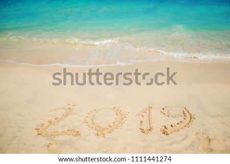 Sea surf. A blue wave is coming ashore. Inscription on the sand, celebrate the new year in the tropics. New year holidays #1111441274