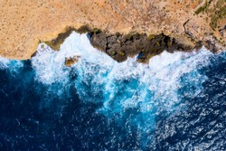 Sea surf. Aerial view. From above. Sea surf background. Blue waves at rocky seashore top view. Rocky coastline.