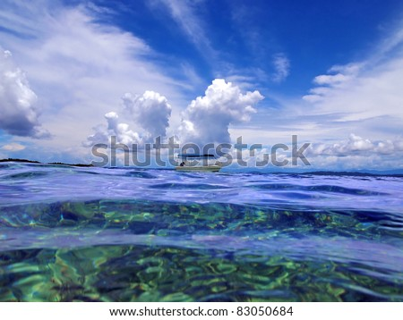 Sea surface with boat and cloudy blue sky on the horizon, Caribbean sea, Panama