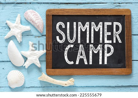 Sea travel frame decor with seashells over wooden background with small blackboard with text Summer camp