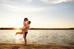 Sea travel, happy couple hugging on sea side near hot summer water of ocean. Honeymoon picture with copy space