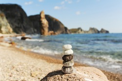 sea urchin shells stand harmoniously stacked on rock against a gorgeous seascape with azure water and high rocks, selective focus