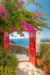 Sea view and architecture in Thira, Santorini, Greece. Beautiful vertical banner for luxury travel and summer vacation. Beautiful pink flowers with red wooden gate over the caldera and wall exterior