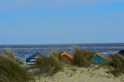 Sea view at Southwold, Suffolk, east Coast of England. Showing the tops of 3 colourfully painted beach huts behind the sand dune. Clear blue spring sky.